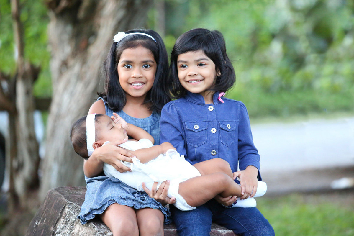 Two young girls dressed in blue holding a baby in white. Photo by Ross Photography, Trinidad, W.I..