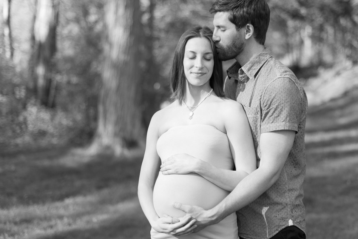 Black and white of maternity session with mother and father holding pregnant belly in at home session in Armonk, NY photo