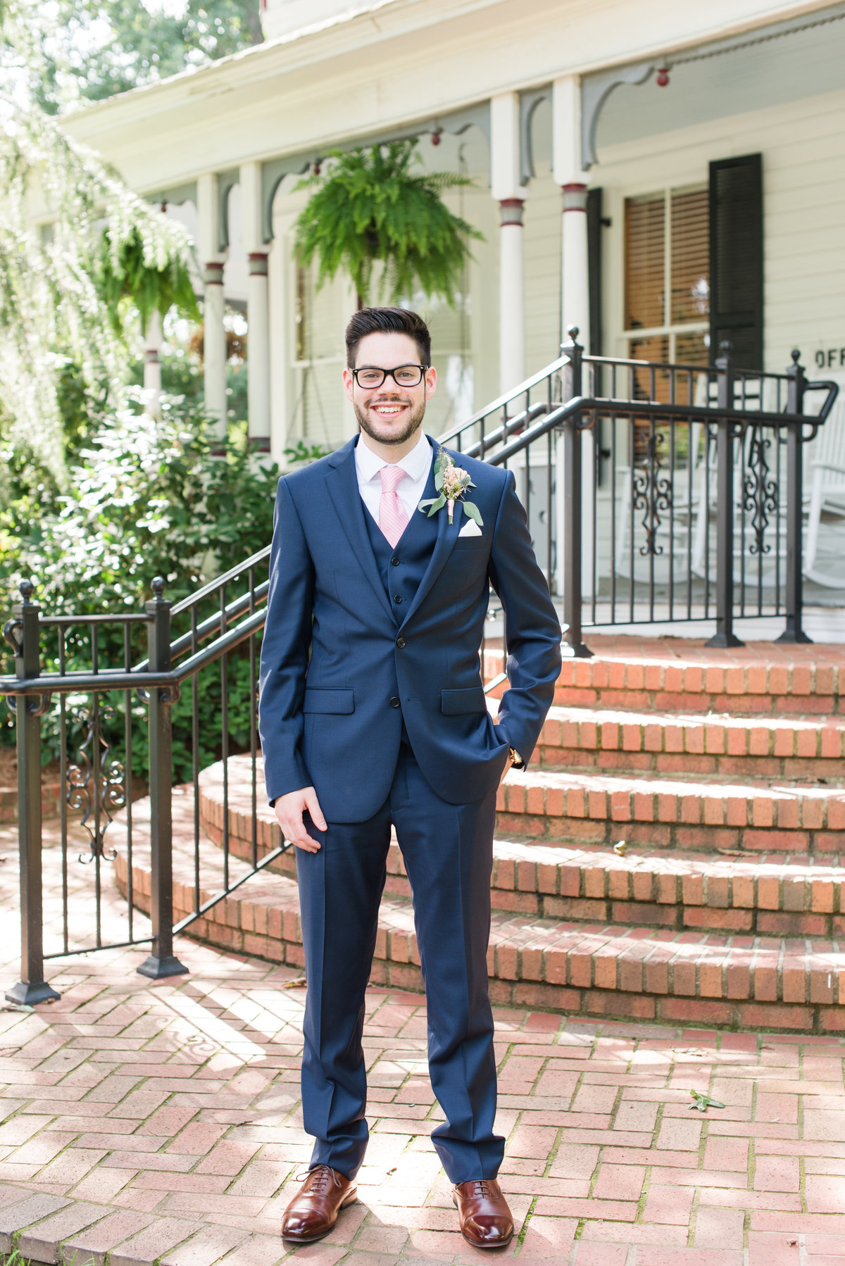 Groom wearing navy blue suit with pink tie with one hang in pocket looking at the camera standing in front of the main house at Gardens at Gray Gables