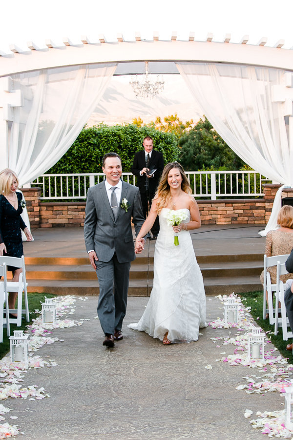 Newly weds walking down the isle holding hands at Mountain Meadows Golf Drive