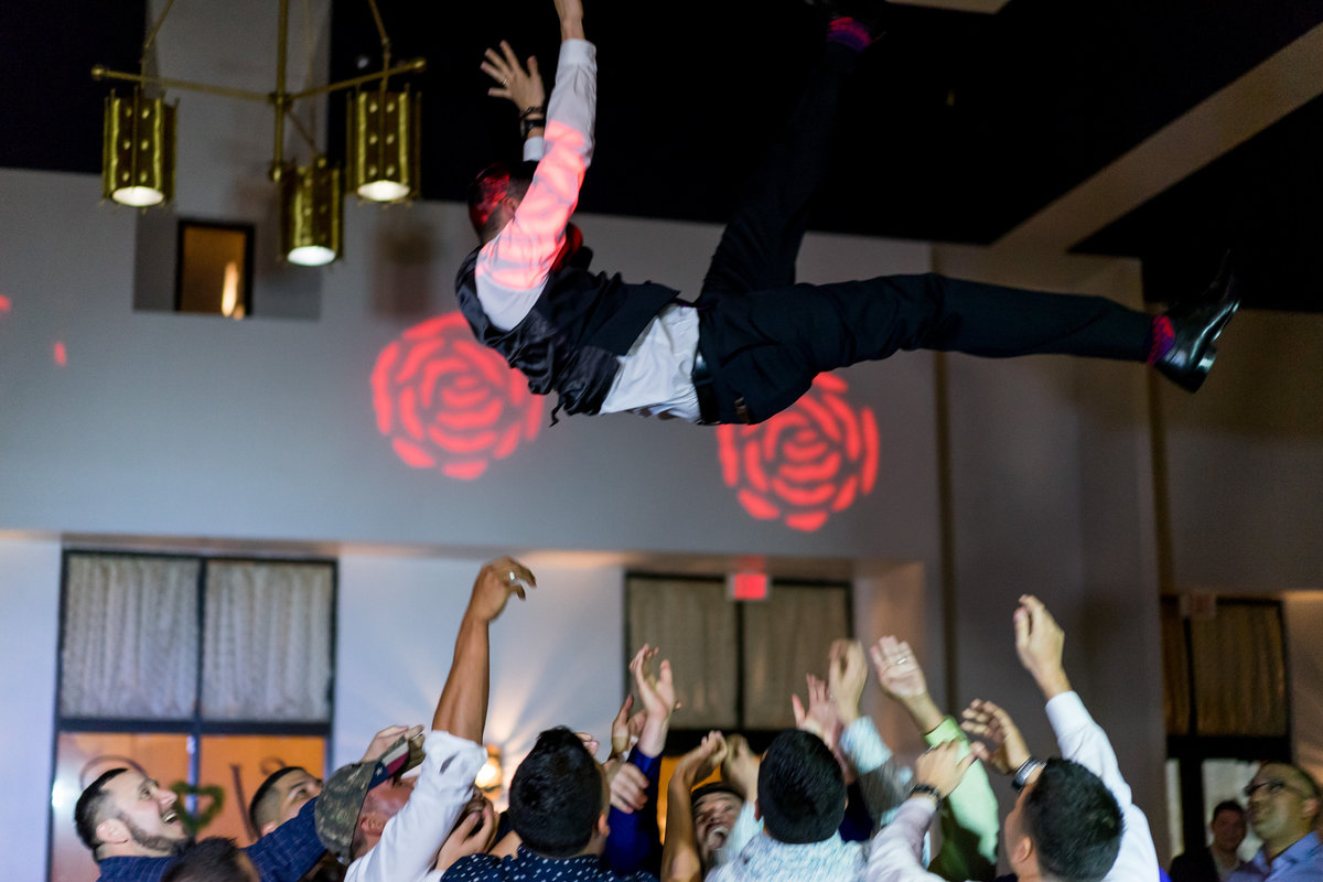 wedding guests toss groom in air during wedding reception at San Fernando Hall in down town San Antonio
