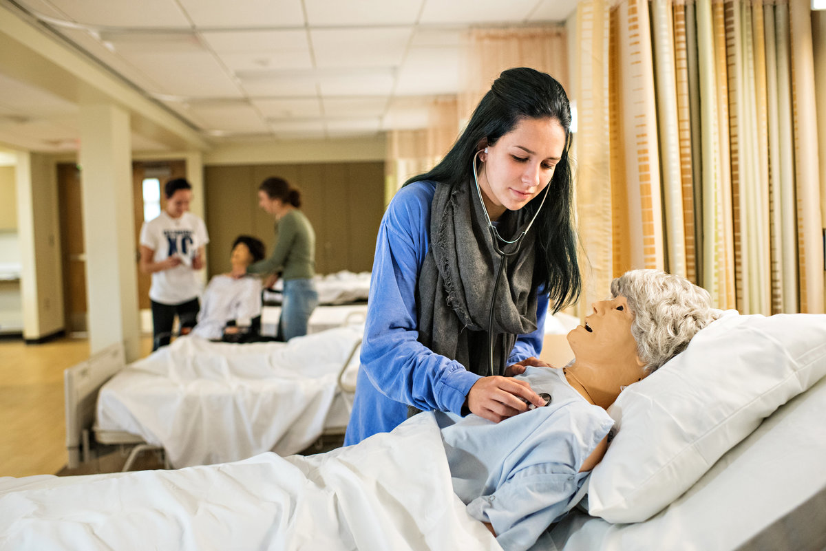 A nursing student practices on a dummy  for a college nursing program.