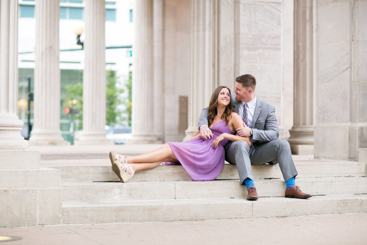 Bride and groom cuddling on steps at civic Center Park in Denver