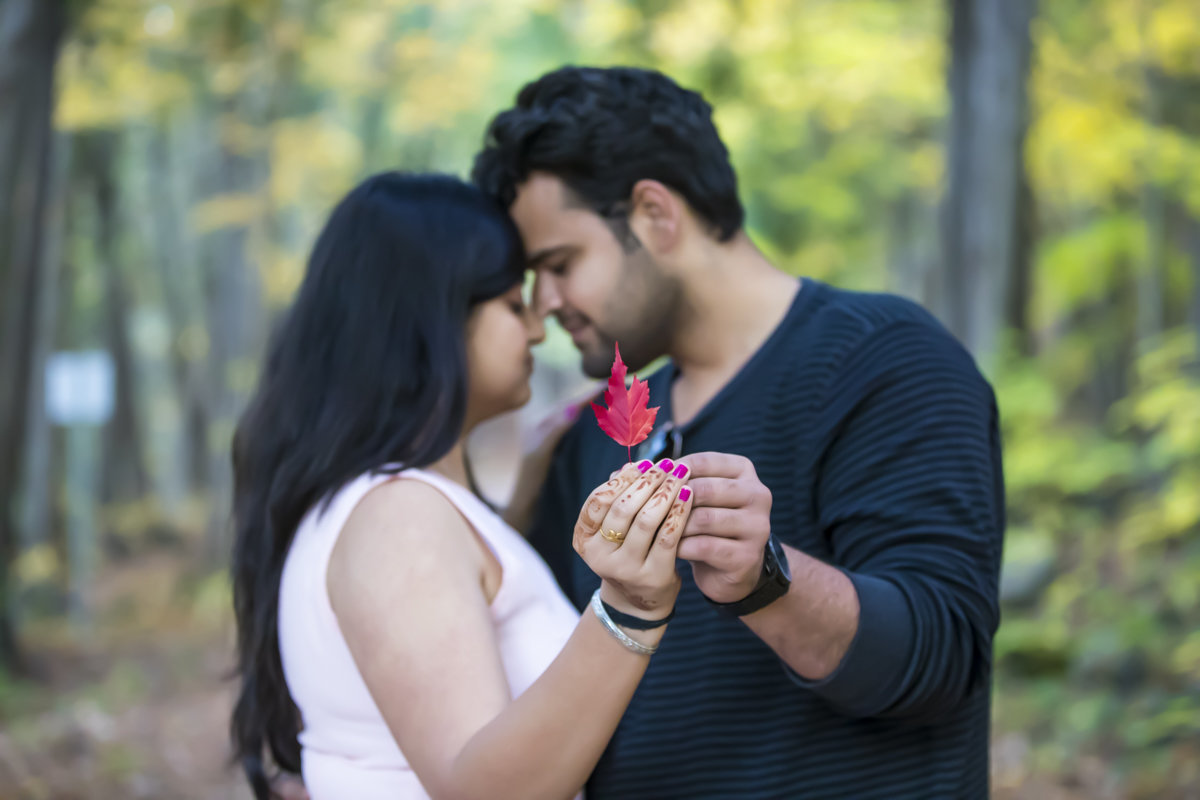 engaged couple embrace each other while holding out a red leaf in front of them while they have their foreheads touching