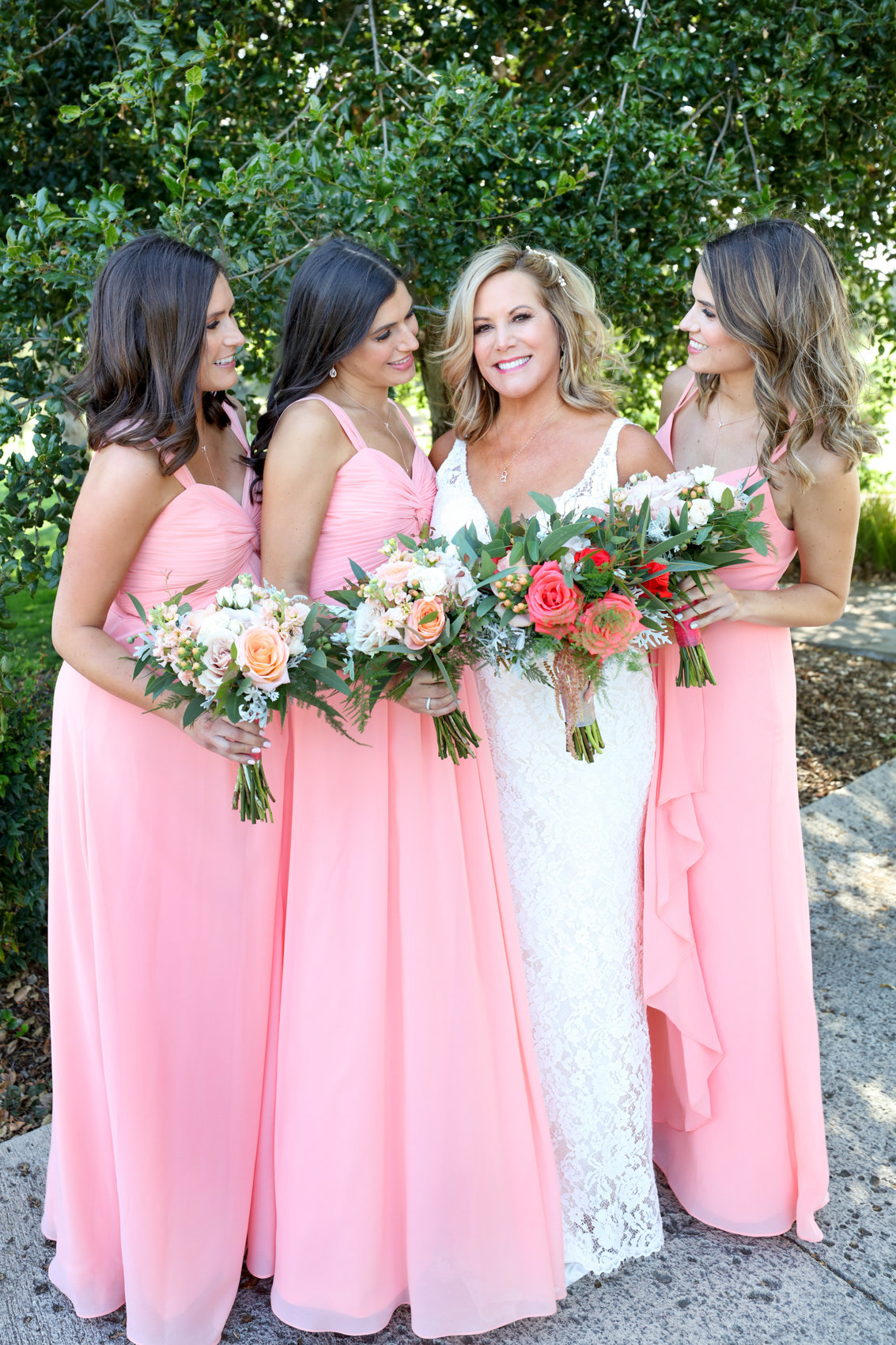 Portraits of bride with bridesmaids holding bouquets, outdoor portraits before wedding