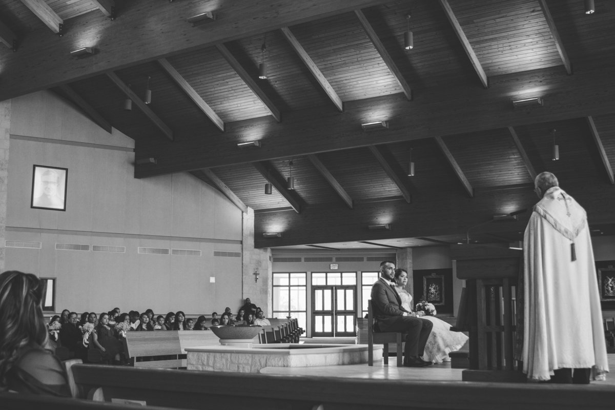 couple sitting at alter during wedding ceremony at St. Anthony Claret Catholic Church San Antonio