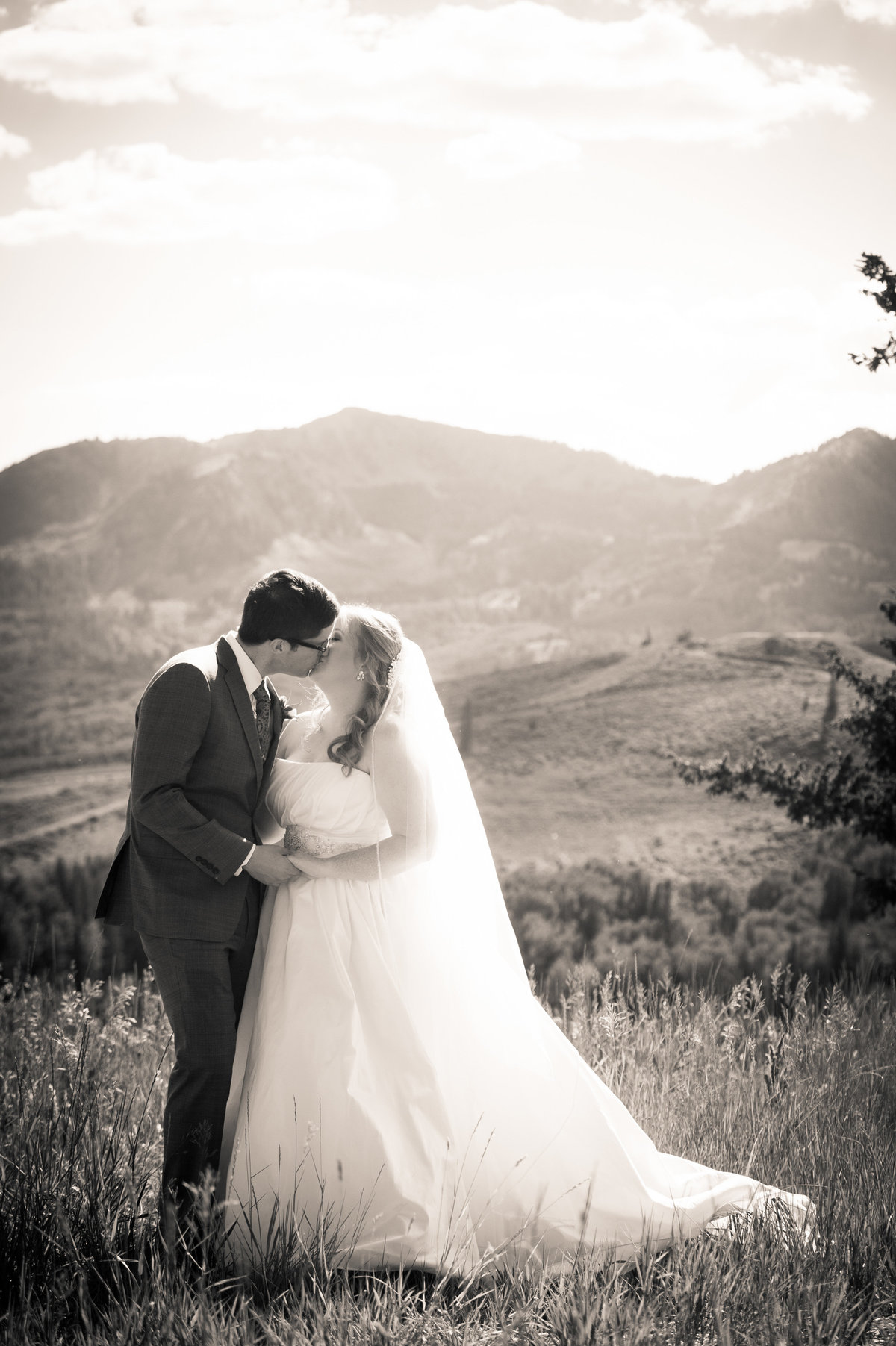 Park City, Utah, couple kisses against mountain background, just married.