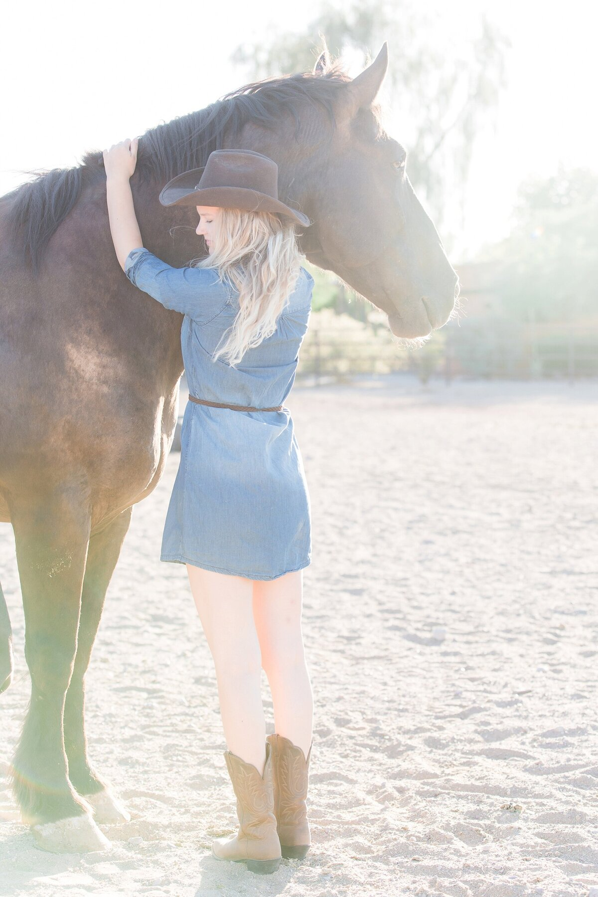 cowgirl standing in front of her draft horse as he's looking away and she's looking down