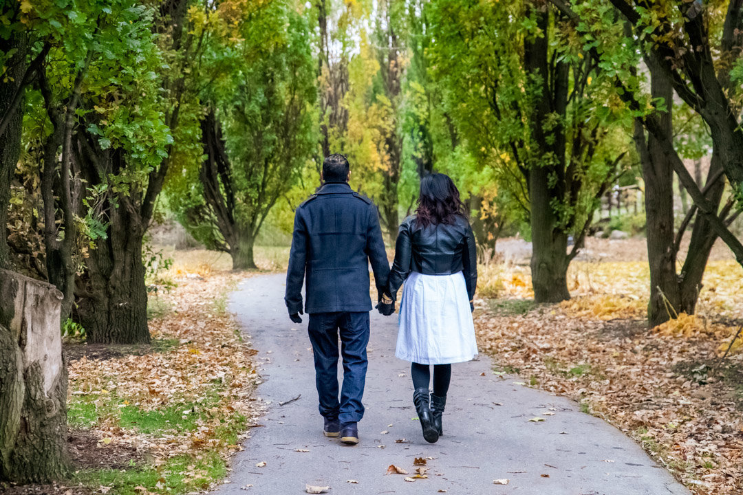Couple walking away down a path with fall leaves on the ground at Chinguacousy Park in Brampton