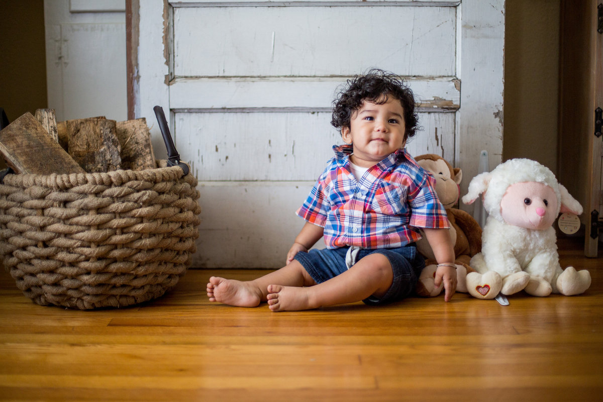 Baby sitting on wood floor in front of a door and with lamb prop next to him.