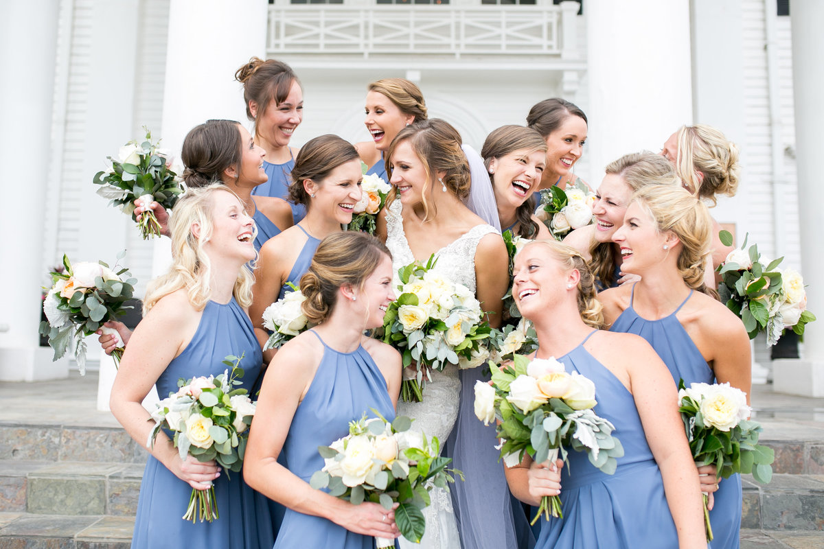 Bride with all her bridesmaids laughing together