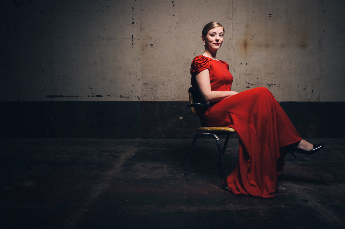 Woman seated in basement with red dress, musician, Chicago.