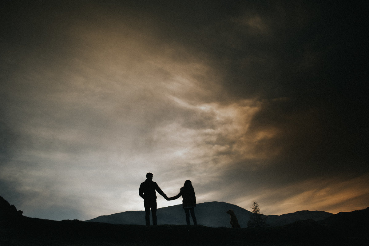 Engaged Couple holding hands in Lake District  silloetted at sunset by Lancashire Wedding Photographer Jono Symonds