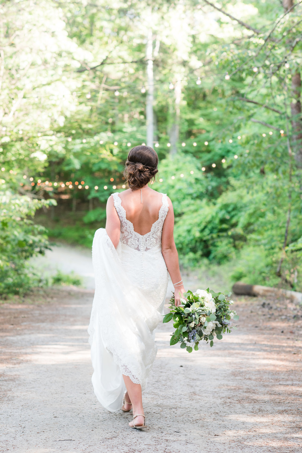 a bride wearing a laced thin strapped wedding dress holding a lush green and white wedding bouquet walking down a walk way with twinkle lights behind her at Meadows at Walnut Cove