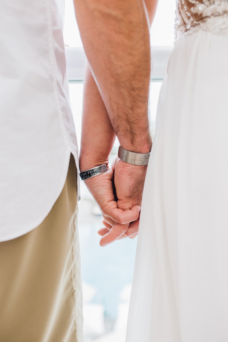 couple holding hands wearing military memorial bracelets