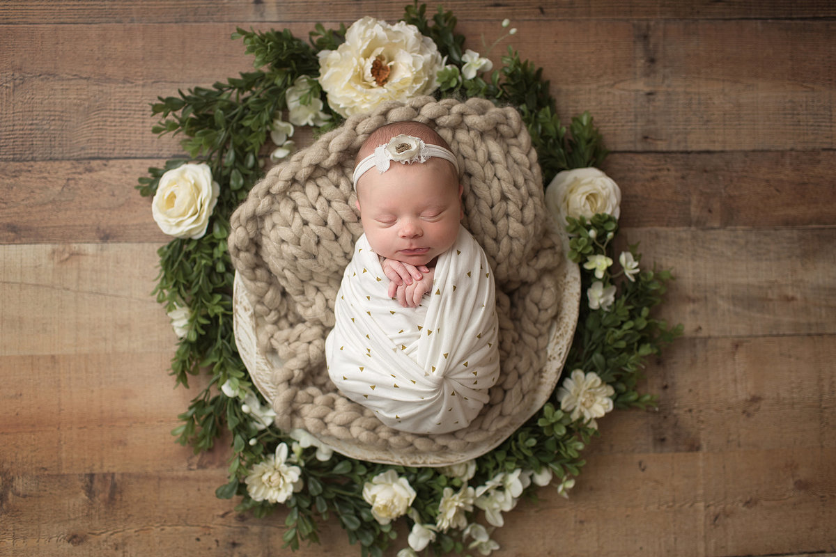 Lancaster infant wrapped and laying in wood bowl with flowers