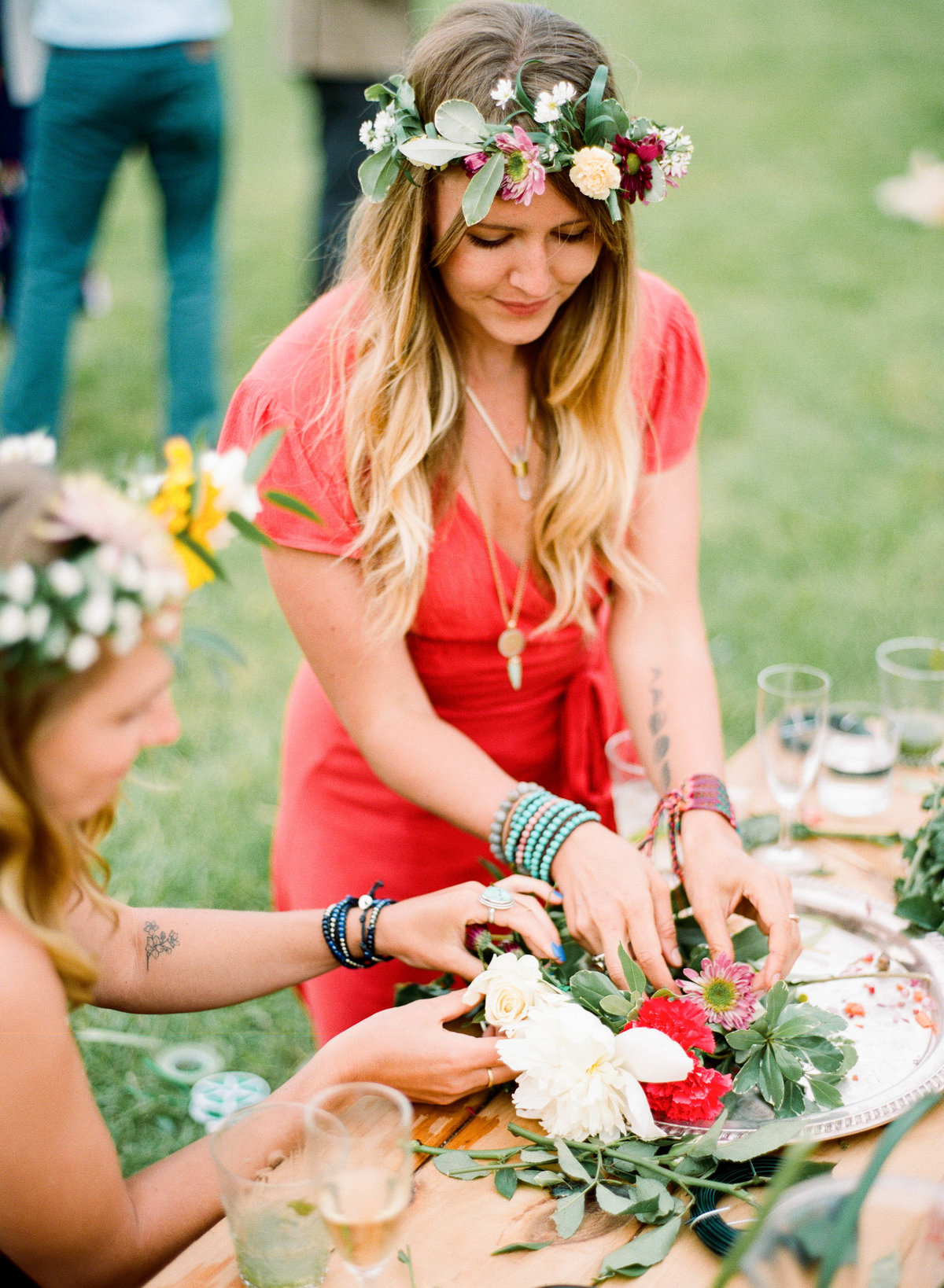 boho girl making flower crowns at wedding