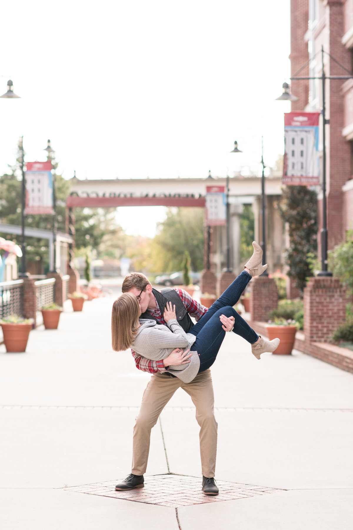 an engagement session at American Tobacco Campus with a guy holding onto and dipping his fiance for a kiss in Durham NC
