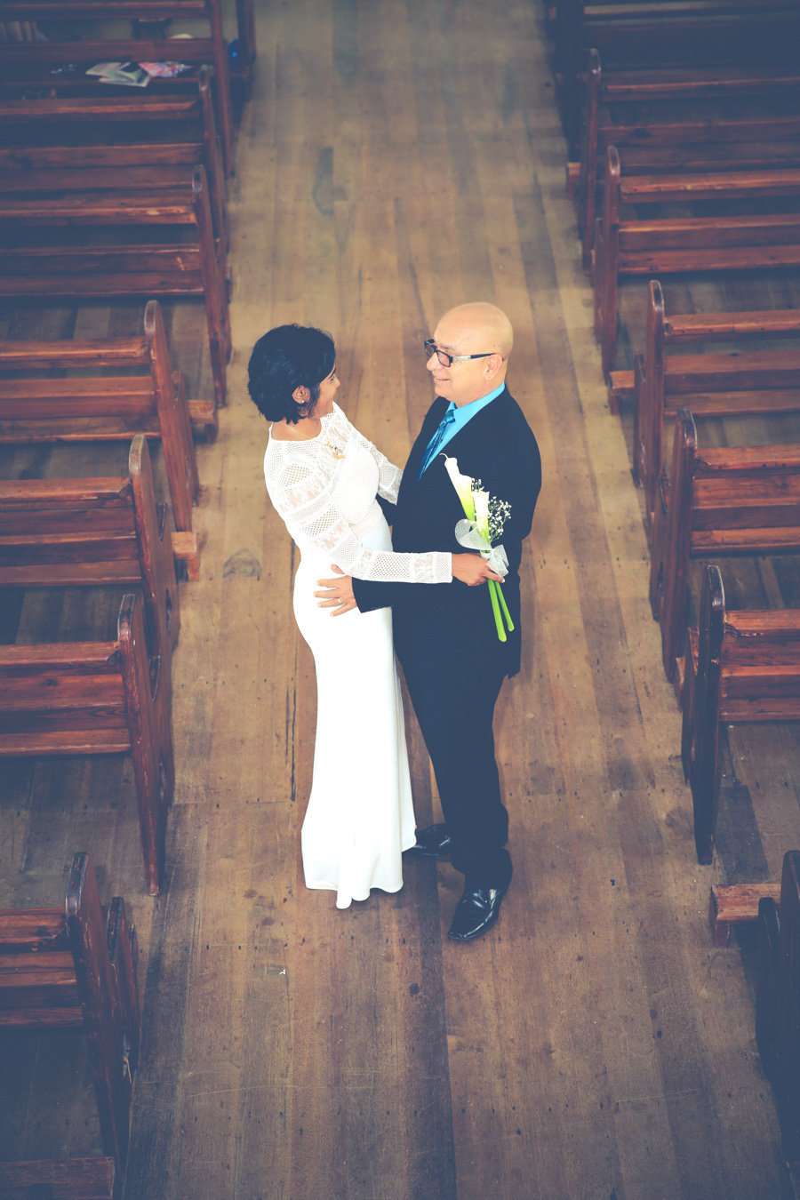 Bride and father-of-the-bride share a moment in church aisle. Photo by Ross Photography, Trinidad, W.I..