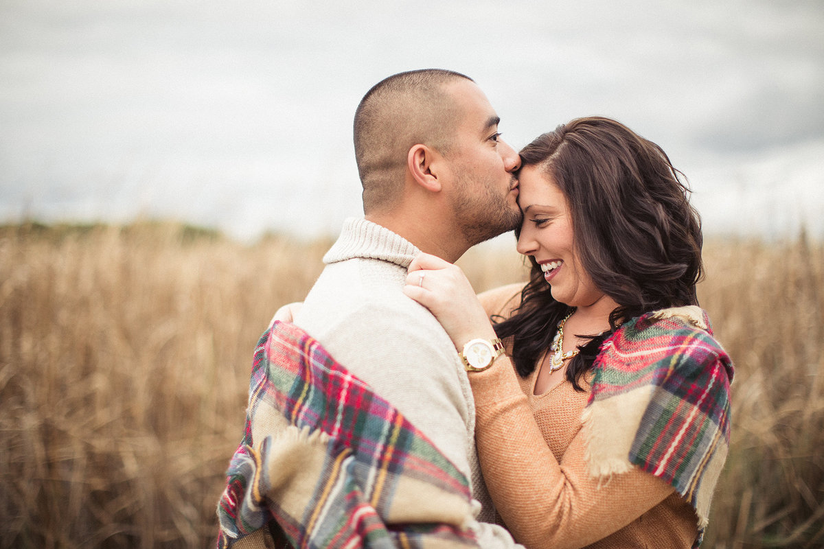 man kissing the forehead of his fiance during an engagement session in fall