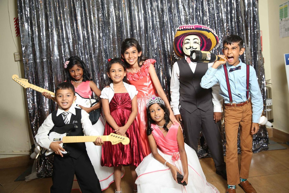 Young children pose in front of silver backdrop wearing masks and hats and holding fun props. Photobooth by Ross Photography, Trinidad, W.I..