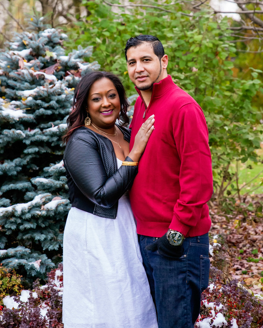 West Indian couple standing in front of trees at Chinguacousy Park in Brampton with girls hand on guys chest
