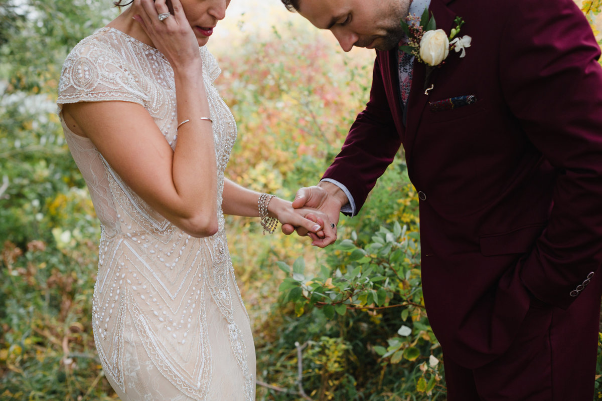 Maroon groom suit. Bride and groom holding hands
