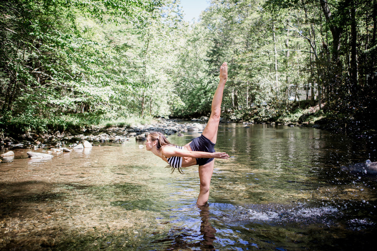 Ballerina standing in the Little Pigeon River doing a dance move in Gatlinburg, TN for her senior pictures by Knoxville Wedding Photographer, Amanda May Photos.