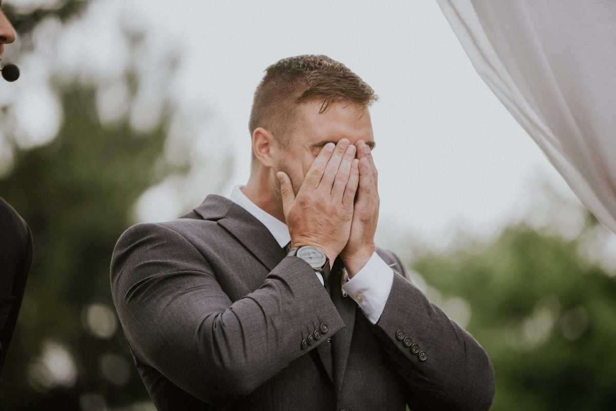 Groom covers his eyes after seeing his bride at their mustard seed gardens wedding ceremony