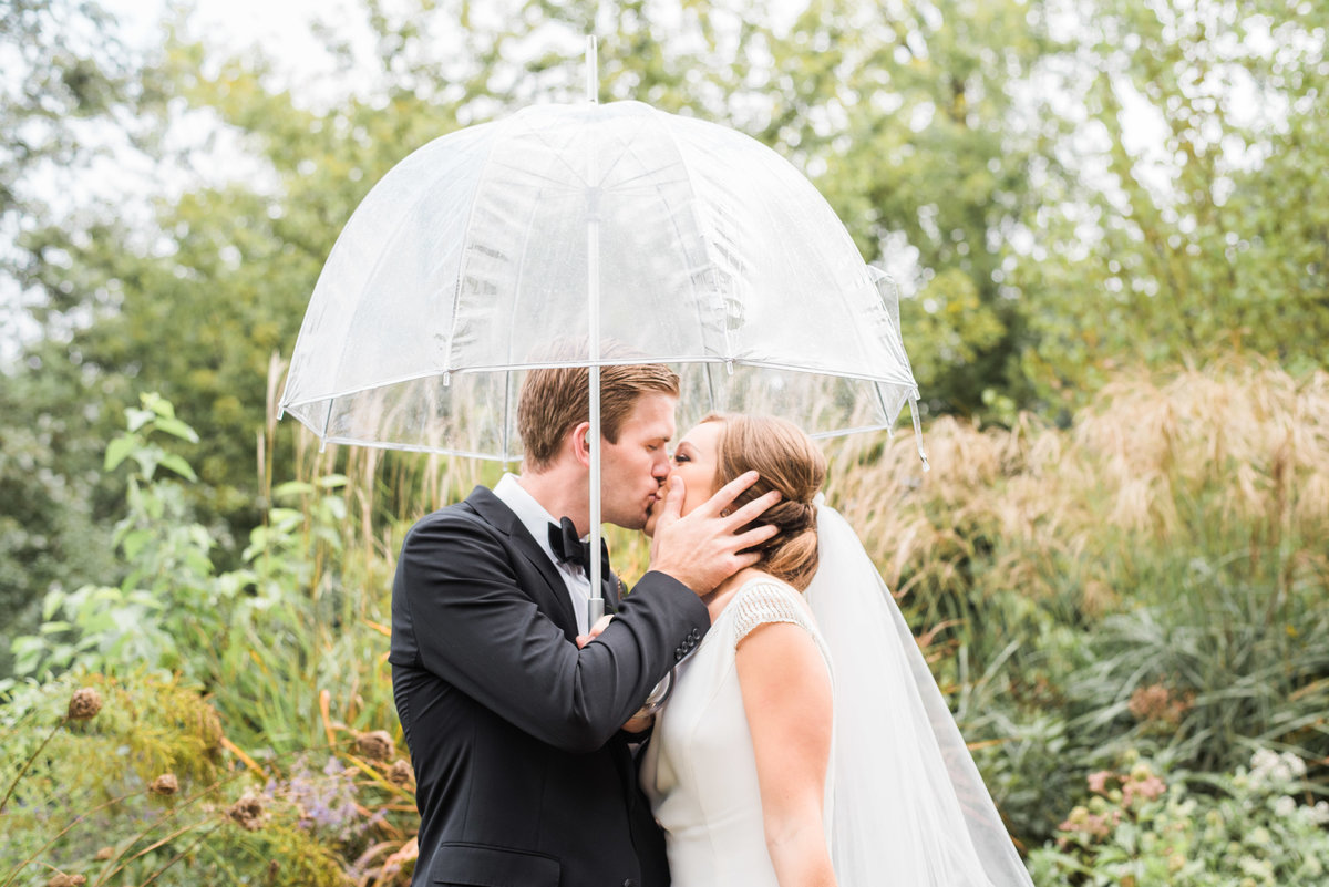 bride and groom kissing under umbrella
