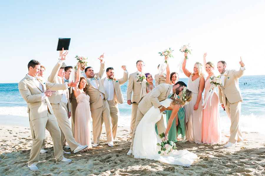 beach portrait of newly weds kissing with bridal party cheering them on
