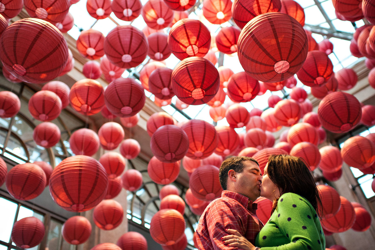 An engaged couple kiss under a paper lantern exhibit at longwood gardens in west chester, PA.