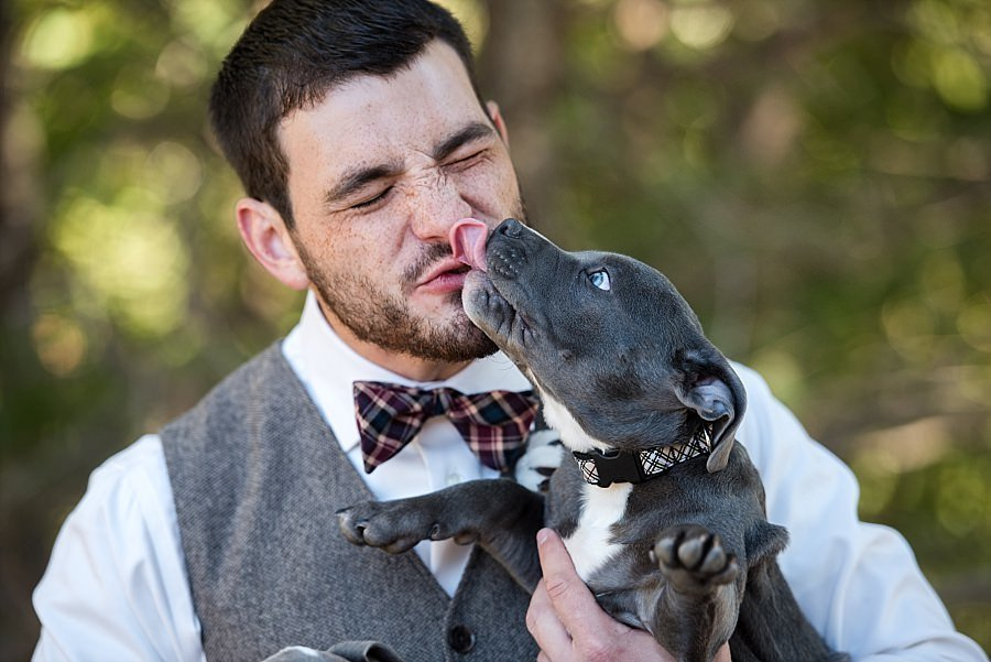 Dog giving groom a kiss before he walks down the aisle to marry his bride