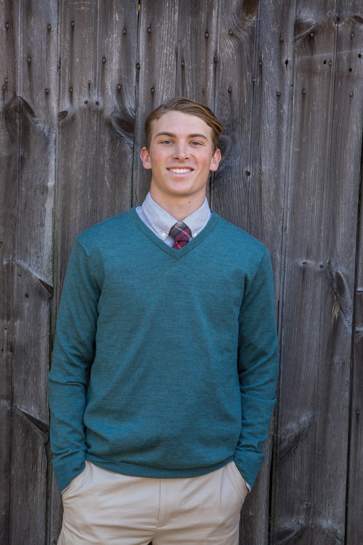 senior portrait in front of barn