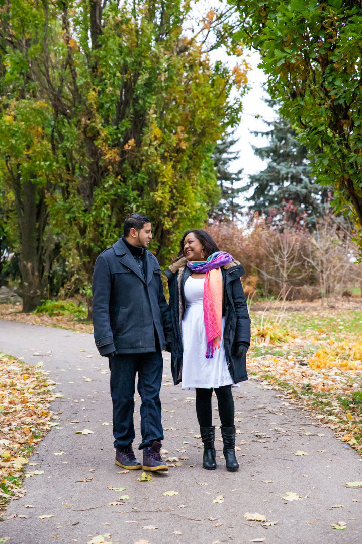 Couple walking on the path at Chinguacousy Park in Brampton with the fall coloured trees around them