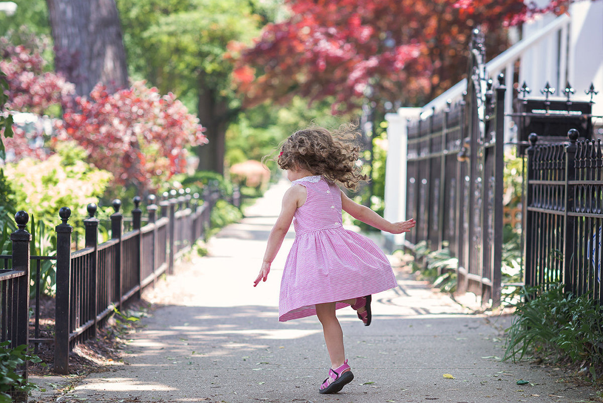 a little girl does twirls in a pink dress