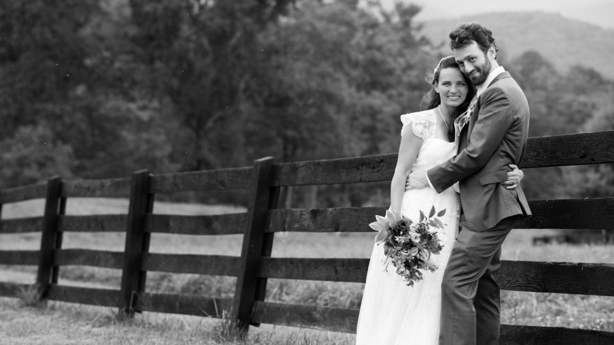 Bride and groom embrace by fence, Charlottesville VA.