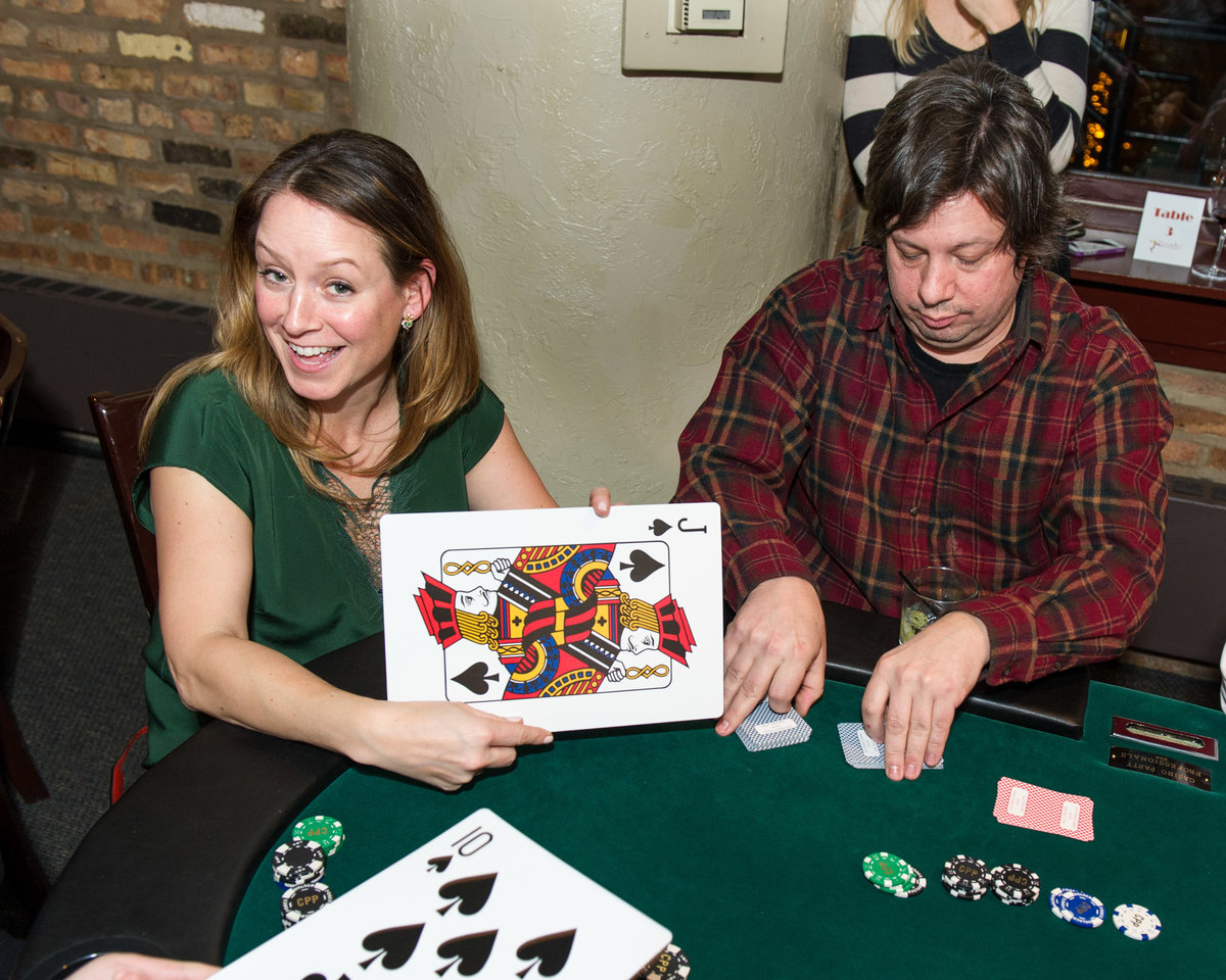 Guest shows off oversized playing card, fundraising event, Chicago IL.