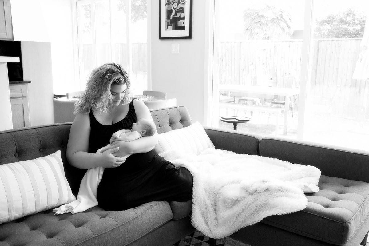 Black and white photo of a mom holding her baby girl in their living room full of light sitting on their modern style lounge sofa