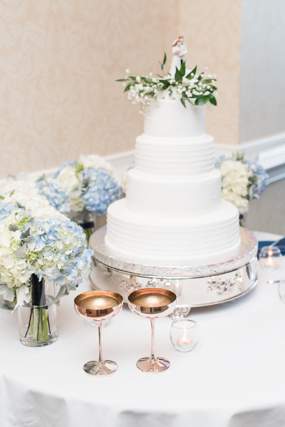 a white four tiered layered wedding cake with blue and white hydrangeas surrounding the cake with old vintage champagne glasses at North Hills Country Club in Raleigh NC