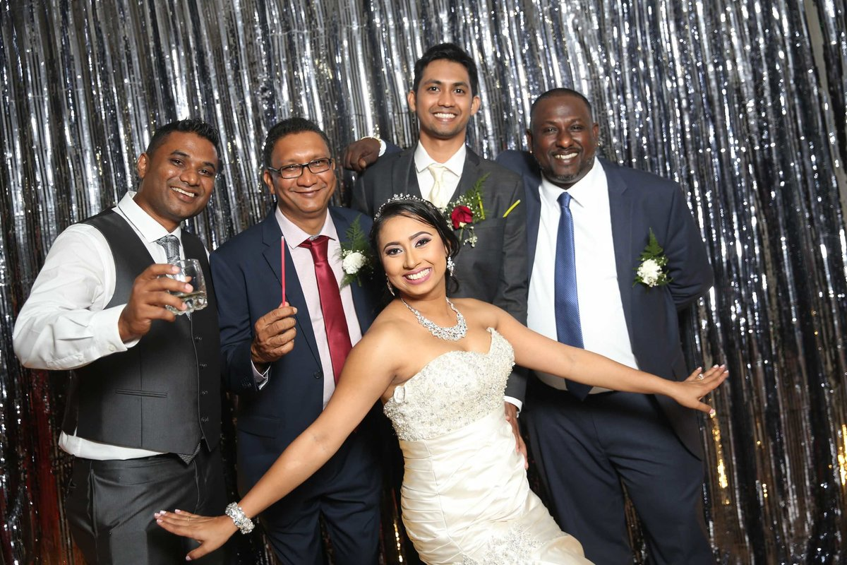 Bride poses with groom and groomsmen. Photobooth by Ross Photography, Trinidad, W.I..