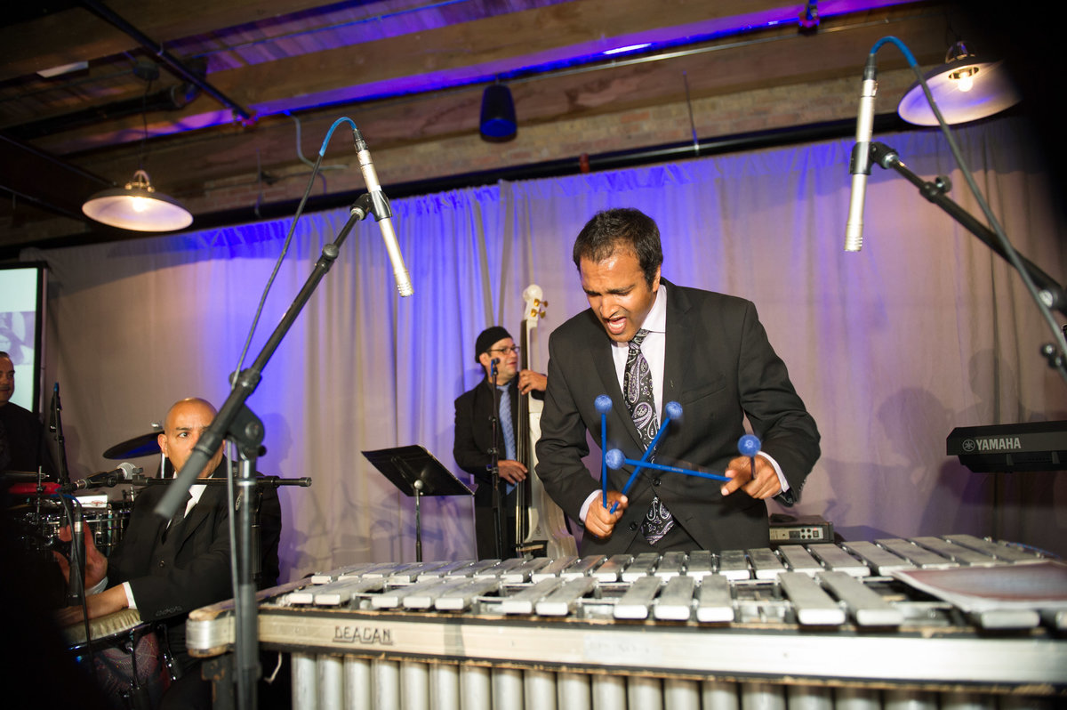 Bandmember plays xylophone at Chicago fundraising event.