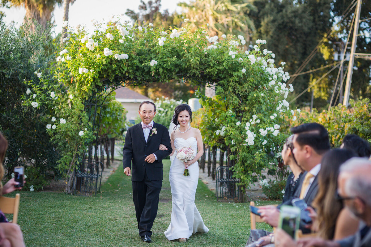 bride being walked down the aisle by her dad
