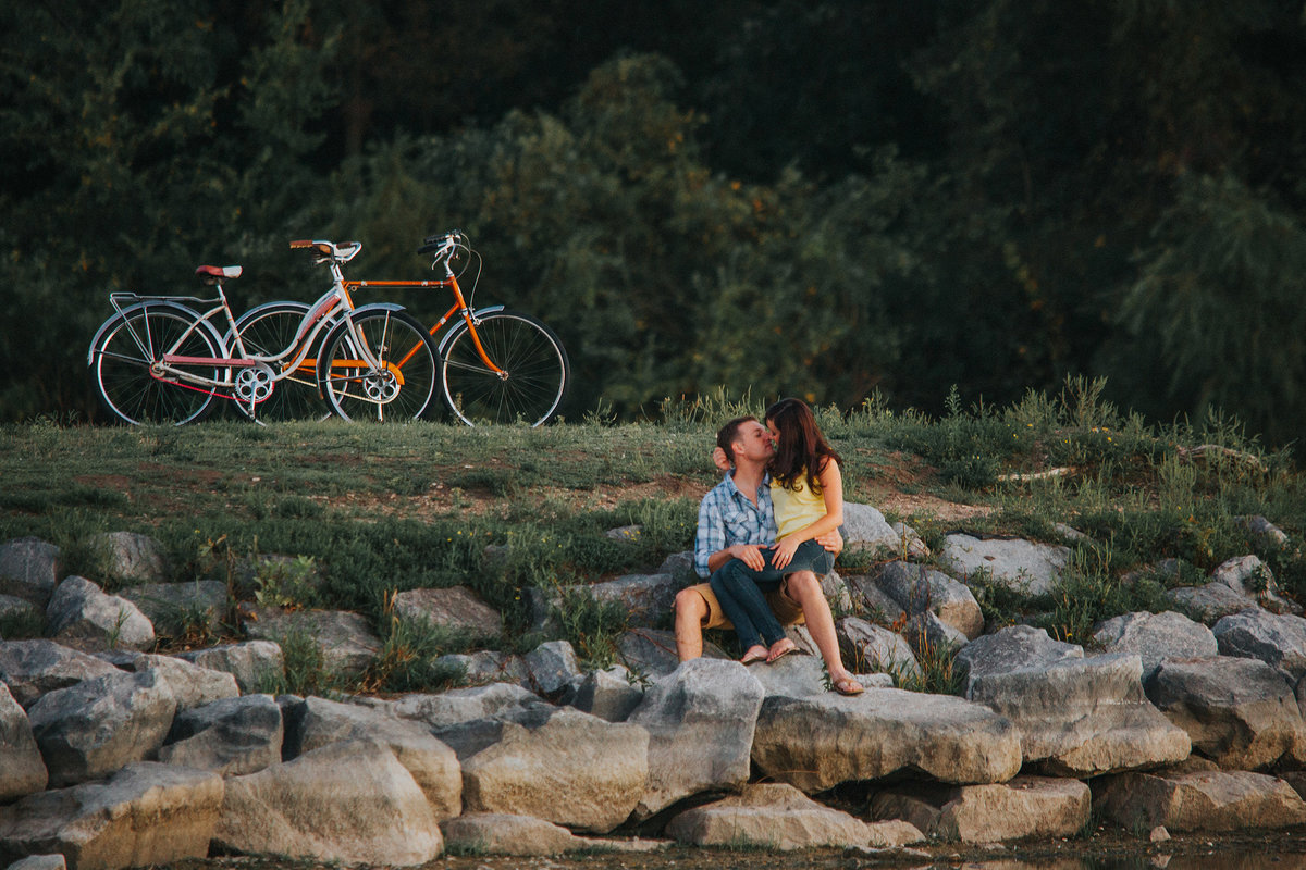 couple cuddling after a vintage bike ride along a lake