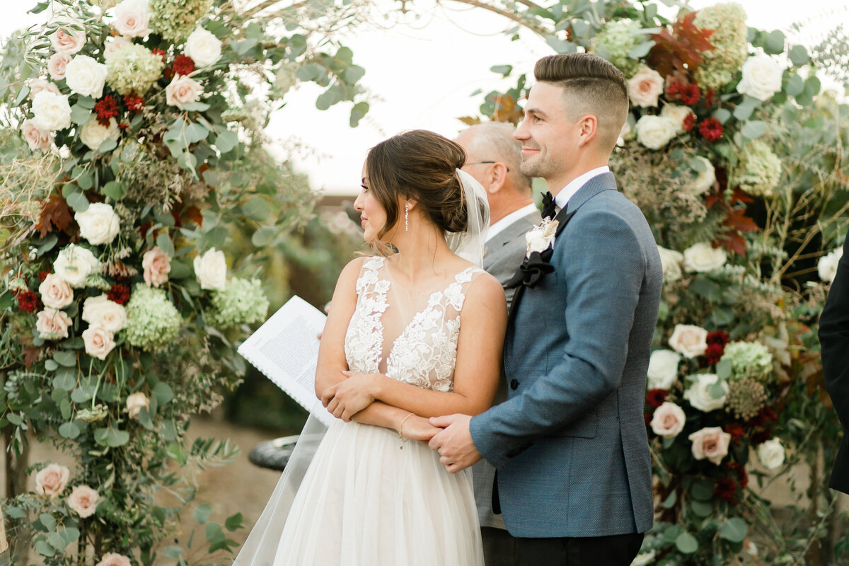bride and groom standing under a full arch of flowers