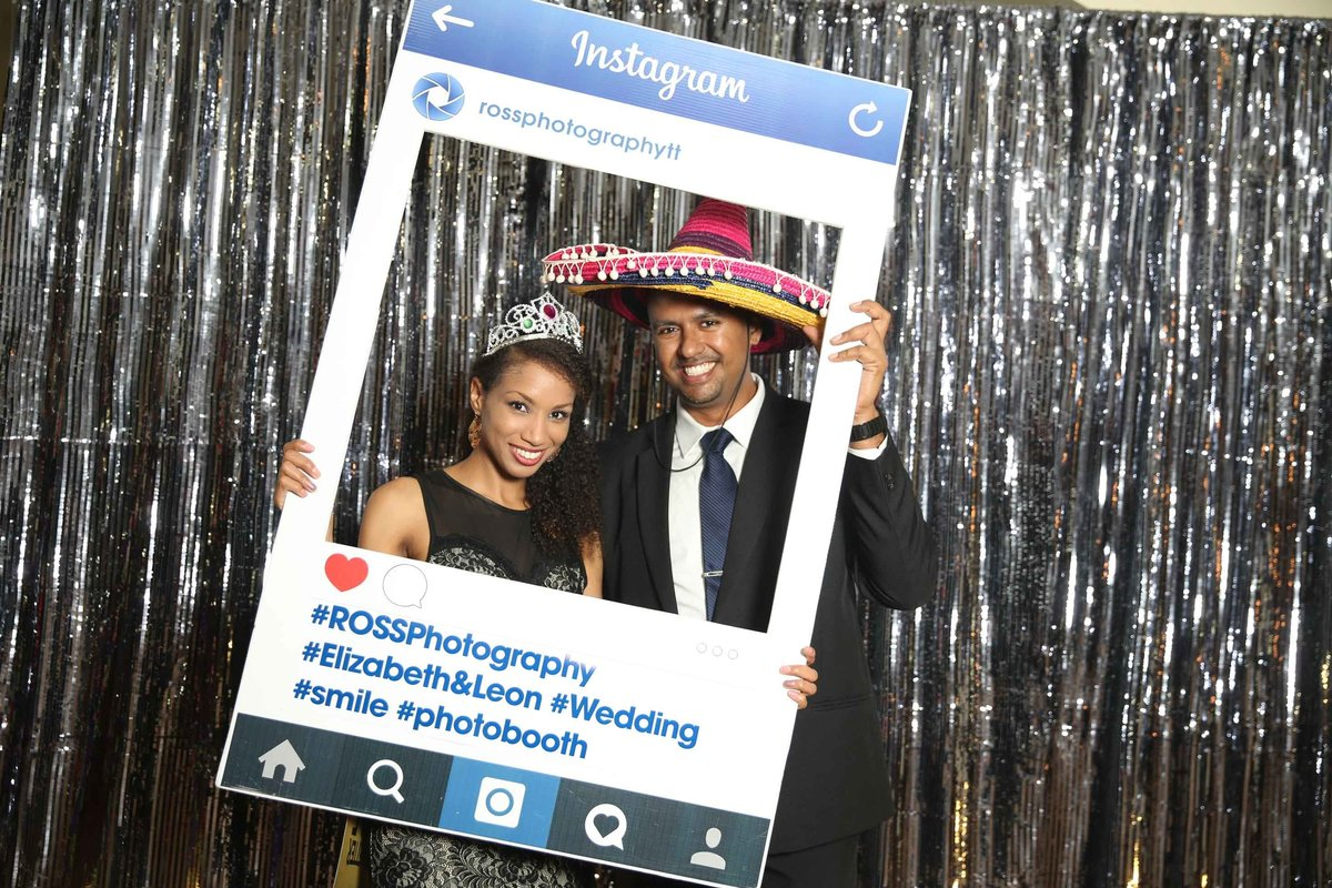 Couple poses in front of silver backdrop with customized, social media cut-out frame. Photobooth by Ross Photography, Trinidad, W.I..
