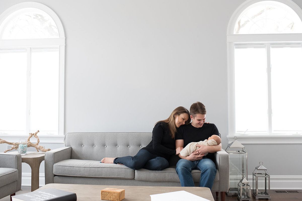 parents look down at their new baby on a gray sofa