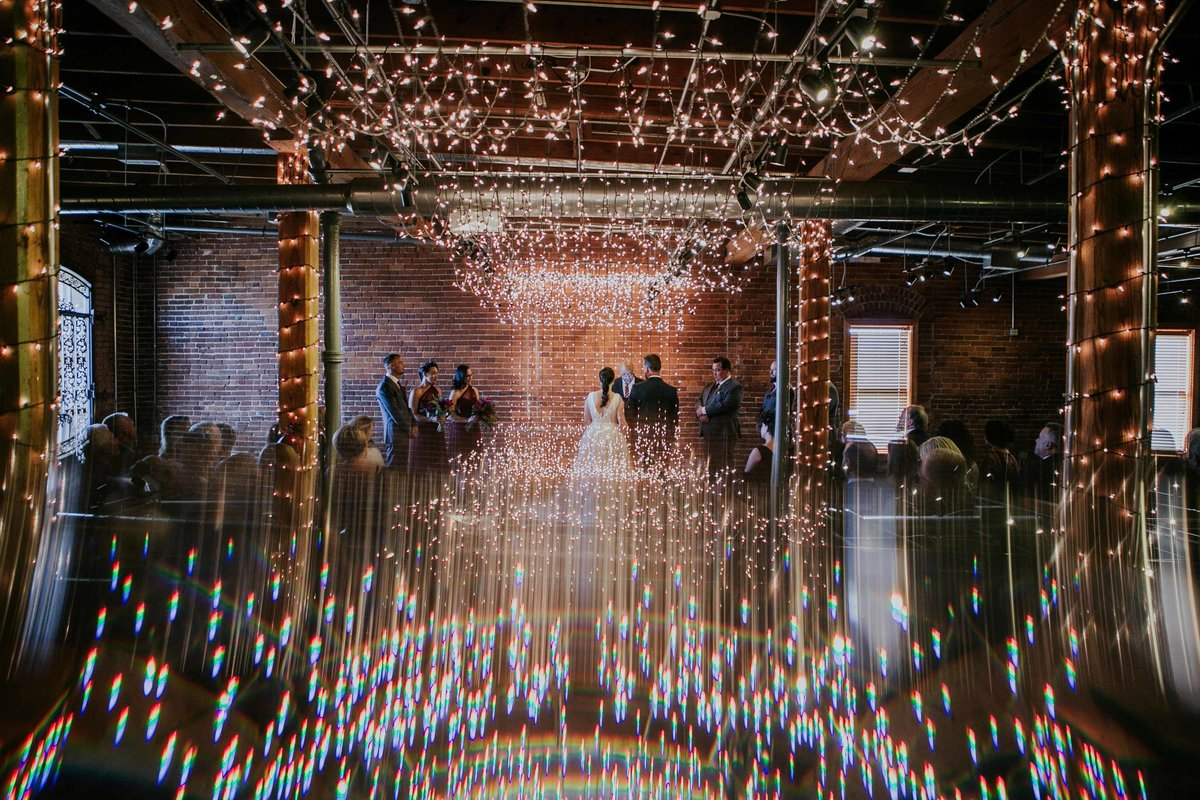 Bride and groom stand surrounded by lights at Milltop wedding in Noblesville