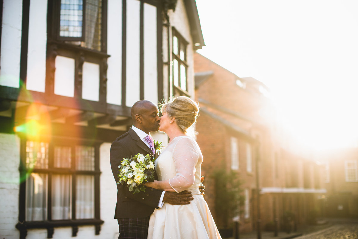 couple kissing next to a tudor building at sunset in chester