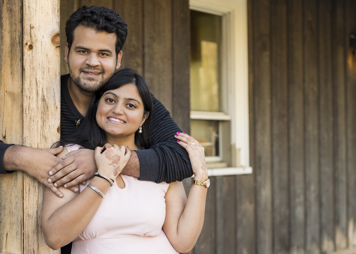 engaged indian couple with grooms arm gently embracing his bride to be around the shoulders with his other arm around a wooden beam at the Forks of the Credit River Conservation Park